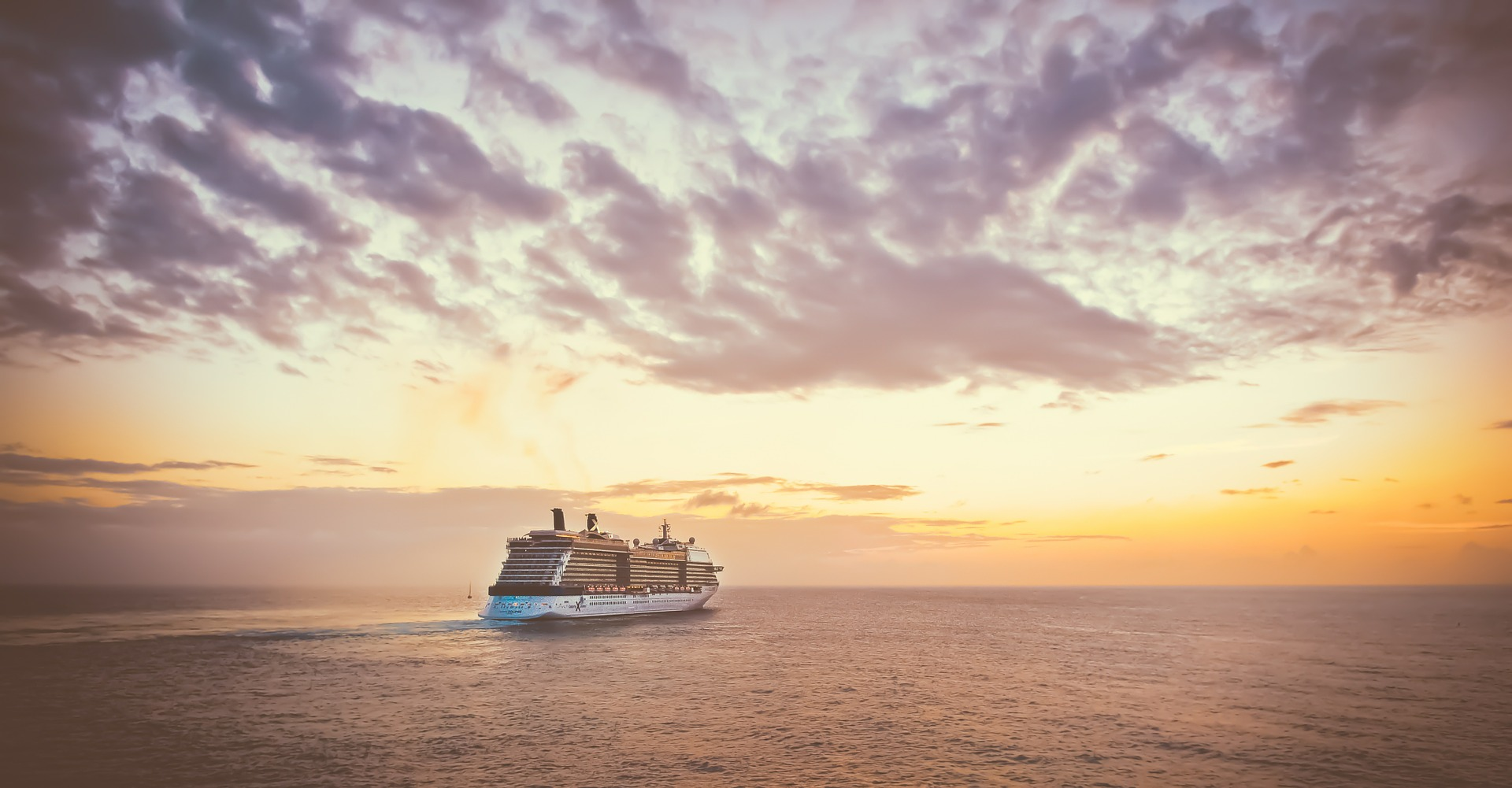 A cruise ship with sunset in the distance